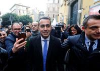 集会会場に到着し、市民やメディアなどに囲まれる「五つ星運動」のディマイオ代表(中央)=ナポリで2月12日、ロイター