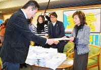 大阪市議会の山下昌彦議長(左)に陳情書を提出する大阪市民会議のメンバー=大阪市役所で、椋田佳代撮影