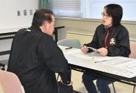 マイナンバーカードの一括申請で宇都宮市の職員(右)に事前に用意した交付申請書類を提出する県職員=宇都宮市の県庁で