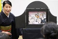 白根園子さんの紙芝居「大工と殿様」の上演に参加者は興味津々=松江市殿町の松江歴史館で、根岸愛実撮影