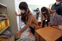 本などが散乱した教室に約7年ぶりに戻り、自分の持ち物を探す当時小学2年の小勝優希さん(手前)=福島県大熊町立大野小学校で2018年3月2日午前10時7分、喜屋武真之介撮影