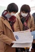 約7年ぶりに戻った教室で自分の持ち物を見つけ、当時を懐かしむ小勝優希さん(左)ら=福島県大熊町立大野小学校で2018年3月2日午前10時7分、喜屋武真之介撮影