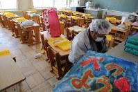 帰還困難区域内の大熊町立大野小学校で、甥らの持ち物を探す男性=福島県大熊町の同校で2018年3月2日午前10時31分、喜屋武真之介撮影