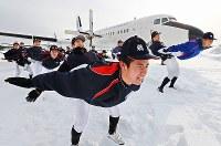 二人一組になり、飛行機の形をする補強運動に汗を流す日本航空の選手たち=石川県輪島市で2017年1月18日、山崎一輝撮影