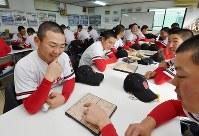 真剣な表情で将棋に取り組むおかやま山陽の選手たち。先の先を読むことや、全体を見ることの訓練になるという=岡山県浅口市で2018年2月4日、川平愛撮影