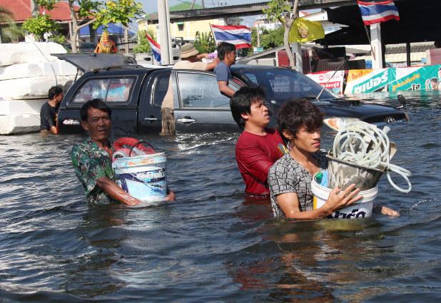 腰の高さまで冠水した道路を歩く人たち=バンコク郊外バンブアトンで2011年11月1日、山本晋撮影