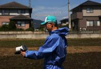 住宅と畑が広がる地域で空間線量を測定する岩手大農学部の佐藤至教授(56)=福島県大熊町で2017年9月10日、小出洋平撮影