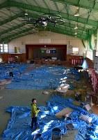 ドローンを使って撮影される町立富岡第二中学校の体育館。東日本大震災からまもなく7年を迎えるが、内部は震災当日の午前中に行われた卒業式の様子と、その夜、周辺住民が避難所として使った跡がそのまま残る=福島県富岡町で2018年3月2日午前8時41分、竹内紀臣撮影