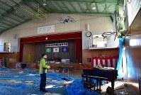 ドローンを使って撮影される町立富岡第二中学校の体育館。東日本大震災からまもなく7年を迎えるが、内部は震災当日の午前中に行われた卒業式の様子と、その夜、周辺住民が避難所として使った跡がそのまま残る=福島県富岡町で2018年3月2日午前8時39分、竹内紀臣撮影