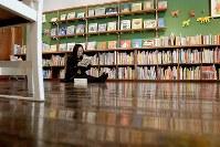 本屋に生まれ変わった教室で、本を読む女性=京都府京丹波町の旧質美小学校で、平川義之撮影