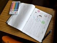 学校を訪れた観光客らの感想がつづられた学級日誌=京都府京丹波町の旧質美小学校で、平川義之撮影