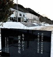 閉校した際に建てられた石碑と旧質美小学校の校舎=京都府京丹波町の旧質美小学校で、平川義之撮影