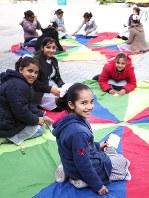 学校の中庭で作業する子どもたち。たことメッセージカードに思いを込める