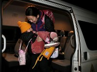 午後6時過ぎ、スクールバスの車内で寝入ってしまった松本澄怜(すみれ)ちゃん(4)は母敦子さん(37)に抱きかかえられながら車を降りた。「子どもを伸び伸び育てたい」と昨年11月に葛尾村への帰還を決めたが、4月に村内の幼稚園が開園されるまで、片道40分かけて三春町の幼稚園に通っている。朝は午前6時に起床し送迎のバスで登園している=福島県葛尾村で2018年2月20日、小出洋平撮影