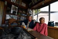 避難指示が解除され、浪江町の自宅に戻った小野田秀一さん(70)左と妻いく子さん(70)。二本松市での避難生活中に認知症を患ったいく子さんのことを考え、ふるさとへの帰還を決めた。避難先ではふさぎ込むこともあったいく子さんだったが、住み慣れた自宅に戻ると笑顔が見られるようになった。自宅脇には除染で出た廃棄物が積まれ、近隣の住民は帰ってこないかもしれない。それでも小野田さんは、いく子さんの穏やかな表情を見て「帰ってきてよかったなぁ」と優しく語りかけた福島県浪江町で2017年11月1日、猪飼健史撮影