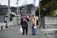 毎週開かれる移動販売から買い物袋を下げて帰り、「またね」と声を掛けて手を合わせる吉田マツイさん(86)=左=と貝塚ヨシさん(91)。南相馬市小高区の自宅に昨年戻った吉田さんは息子夫婦、孫夫婦と3世代で暮らすが、貝塚さんは独り暮らし。「一人で暮らすのは寂しいから散歩の途中なんかに来てくれるとうれしいんだよ」と話す貝塚さん。吉田さんは「ヨシさんの所に行くとお茶を飲むのも忘れて話しちゃうよ」と返して笑ったが、建て直した自宅に帰ることなく避難先で亡くなった夫を思い出すと、涙が出ることもある=2018年2月21日、竹内紀臣撮影