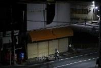 工事関係車両の往来も途絶えた日没後、少ない街明かりの中、震災の爪痕が手つかずのまま残る建物の前をランニングする男性。避難指示が解除された地域でも、原発事故に伴う避難によりシートで覆われ投函できないポストが残っていた=2018年2月5日、小出洋平撮影