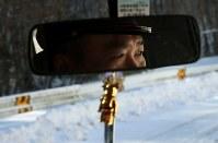 パトロールで雪に覆われ人通りの少ない葛尾村内を運転して見て回る消防団員。団員の多くは避難した田村市や三春町で暮らし、巡回日には避難先から村に戻って1時間ほど担当の地区を回る。第3分団長の松本政利さん(55)は「地元を守りたいという思いで活動している」と話す=2018年2月18日、小出洋平撮影