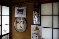 解体を決めた富岡町内の自宅を片付けに訪れ、足を止めて孫の写真に見入る関愛子さん(64)。日めくりカレンダーは震災当日の日付けのまま残されていた。いわき市内で夫友幸さん(72)と暮らす転居先に親族が集まり、家の思い出話になると懐かしさがこみ上げる=2017年8月29日、小出洋平撮影