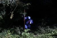 うっそうと雑草が生い茂る浪江町の山林で空間放射線量を計測するため、山に分け入る研究者=福島県浪江町で2017年9月9日、小出洋平撮影