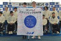 出発セレモニーで応援メッセージが書かれた旗を受け取り写真撮影に応じる平昌パラリンピック日本代表選手団の須藤悟主将(右)=羽田空港で2018年3月3日、西本勝撮影