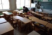 帰還困難区域内の大熊町立大野小学校で、孫らの持ち物を持ち帰る女性=福島県大熊町の同校で2018年3月2日、喜屋武真之介撮影