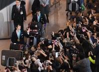 平昌五輪を終えて帰国し、大勢のファンの出迎えを受ける羽生結弦選手(左端)と宇野昌麿選手=成田空港で2018年2月26日、根岸基弘撮影