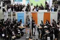 合同企業説明会で、各企業ブースで担当者の話を聞く学生たち=大阪市住之江区のインテックス大阪で2018年3月1日、貝塚太一撮影