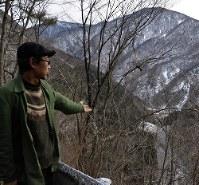 自宅近くの高台から谷あいで進むリニアの工事現場を示す谷口さん=長野県大鹿村で、森健太郎撮影