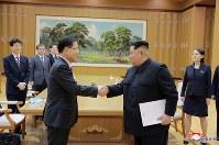 握手する韓国特使の鄭義溶氏(左)と北朝鮮の金正恩氏。右端は正恩氏の妹、金与正氏=平壌で5日、朝鮮中央通信・ロイター