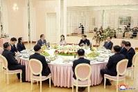 韓国特使の鄭義溶氏らと夕食会で談笑する、北朝鮮の金正恩氏(中央)ら=平壌で5日、朝鮮中央通信・ロイター