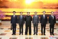 韓国特使の鄭義溶氏らと記念撮影に臨む、北朝鮮の金正恩氏(左から3人目)=平壌で5日、朝鮮中央通信・ロイター