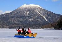 雄阿寒岳を背景に阿寒湖の氷上をバナナボートで走る観光客=北海道釧路市で2018年1月31日、梅村直承撮影
