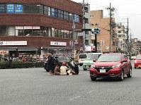車が行き交う百万遍交差点にこたつを持ち込んだ若者ら=京都市左京区で2018年2月25日、通行人提供(画像の一部を加工しています)