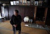 今なお帰還困難区域になっている福島県浪江町津島地区の自宅に、約1年ぶりに戻った紺野礼子さん(83)。同地区には4つの集落にそれぞれ異なる田植え踊りが伝わり、「庭元」と呼ばれる家が踊りの世話役を代々務めてきた。踊りを担う男衆は庭元の家の広間で練習を重ね、その間の食事などは庭元の女性たちが用意した。礼子さんは南津島集落の庭元だった紺野家で生まれ育って婿養子ももらい、長年裏方として田植え踊りを支えてきた。しかし、原発事故に伴う避難で踊りを再開するめどは立たず、家もイノシシなどに入られて荒れてしまった。「もうこの年だし、戻ることは諦めた。でも、この家だけは壊したくない」。声を震わせ、何度も涙をぬぐった=2018年2月26日、喜屋武真之介撮影
