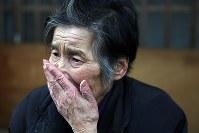 帰還困難区域の自宅前で涙をぬぐう紺野礼子さん(83)。「もうこの年だし、戻ることは諦めた。でも、この家だけは壊したくない」と声を震わせた=2018年2月26日、喜屋武真之介撮影
