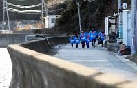 宮城県南三陸町寄木地区の伝統行事「寄木のささよ」で大漁旗を担ぎ、唄い込みをしながら高台の家を回る小中学生たち。今年の参加者は6人だったが、来年は中学3年生が抜けて4人になる。地区は高台に集団移転し、海沿いは今も津波の爪痕が色濃く残る。同町の人口は震災前に比べて3割近く減少した=2018年1月15日、喜屋武真之介撮影