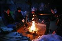 宮城県東松島市月浜地区に伝わる国重要無形民俗文化財「月浜のえんずのわり」で、暖を取るために火をおこす4人。えんずのわりは小中学生の男子が小正月に合わせて6日間、学校に通いながら岩屋で共同生活を送り、1月14日には集落の各戸を回り唱え言をして無病息災などを願う。同地区は津波で多くの家が流され転出が相次ぎ、住民は震災前の半数以下の80人ほどに。子供も減り、来年の参加者は2人だけになる可能性がある=2018年1月12日、喜屋武真之介撮影