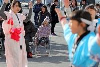 寄磯大黒舞を舞う小中学生の姿を最前列の席で見つめる渡辺羽海ちゃん(6)=中央=。来年は同地区唯一の小学1年生として羽海ちゃんも加わる一方、6年生2人が抜けて小学生だけで七福神を維持できなくなる見通しで、存続が危ぶまれている=2018年1月5日、喜屋武真之介撮影