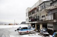岩手県大槌町赤浜地区にある岡本大作さん(69)の元自宅に入る前、2階の入り口で「舞い込み」をする鵜鳥神楽のメンバー。津波は3階天井まで押し寄せたが建物は奇跡的に残り、現在は岡本さんらが3階を地域の伝統芸能の活動拠点などに活用している。鵜鳥神楽は同県の漁師らから信仰を集める同県普代村の鵜鳥神社に伝わる神楽で、普代村から南下する「南回り」と北上する「北回り」を1年ごとに交互に繰り返し、沿岸部の「神楽宿」と呼ばれる民家や公民館を回り舞を披露している。しかし、南回りで訪れる大槌町や釜石市などでは津波で流され途絶えた神楽宿もあり、披露の場が少なくなっている=2018年2月3日、喜屋武真之介撮影