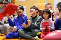 岩手県大槌町赤浜地区にある岡本大作さん(69)の元自宅の3階で披露される鵜鳥神楽の見て、笑顔を見せる地元の子どもたち=2018年2月3日、喜屋武真之介撮影