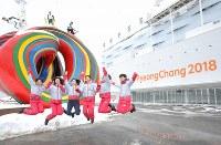 開幕を控え、開会式会場前でジャンプする大会ボランティア=平昌五輪スタジアムで2018年3月8日午後4時9分、宮武祐希撮影