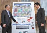 「防犯カメラシステム支援自動販売機」の前に立つ中垣理事長(左)と加地良光・小郡市長