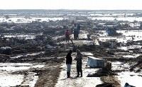 発生から一夜明けた朝、津波の引いた地面に朝日がまぶしく反射する一帯には、ひっくり返った車や大量の流木などが見渡す限り散乱していた。1日にして変わり果てた景色を、地元の人々が心配そうに見回っていた=2011年3月12日午前7時50分、武市公孝撮影