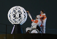 Final torchbearer and wheelchair curler Seo Soon-seok lights the Olympic caldron accompanied by women's Olympic curling silver medalist Kim Eun-jung during the Paralympic Winter Games opening ceremony in the Olympic Stadium in Pyeongchang, South Korea, on March 9, 2018. (Mainichi)