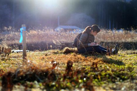 津波で全壊した自宅跡地で小さな花を見つけ、スケッチブックに描き写す三浦菜緒さん。いつかこの場所にラベンダーを植えるつもりだ=宮城県南三陸町で2018年3月4日、喜屋武真之介撮影