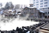 硫黄の匂いと湯気が立ち上る湯畑周辺では、大勢の人々が写真を撮影していた。奥の建物は「湯もみと踊り」ショーが開かれる熱乃湯=群馬県草津町で