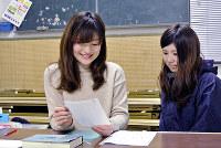 硬筆教室で生徒の作品をチェックする植松里奈さん(左)=徳島県佐那河内村で、倉田陶子撮影