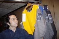「NISHINARI YOSHIO」のタグがついた作品を手にする美術家の西尾美也さん=大阪市西成区のkioku手芸館「たんす」で、岸桂子撮影