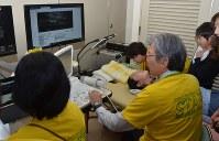 児童の喉に探触子を当てながら検査する野宗義博特任教授(右)=牛久市牛久町で